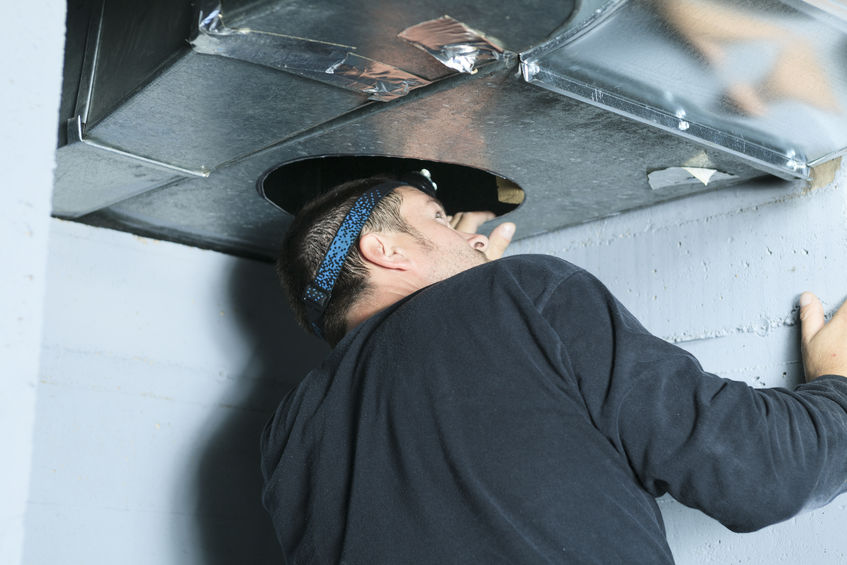 A home inspector checking a vent